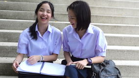 Cute cheerful Asian Thai high schoolgirls student couple in school uniform sit on the stairway having a fun discussing homework. Or exam with a third person stock video