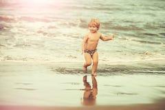 Cute cheerful baby boy runs on wet sand along sea stock photography