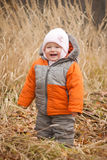 Cute cheerful baby walking in high autumn grass Stock Photo