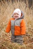 Cute cheerful baby walking in high autumn grass Stock Photo