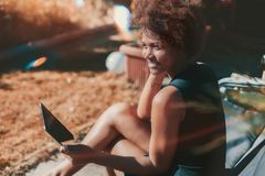 Afro girl in garden with digital tablet. Cute cheerful black teenage female sitting outdoor on armchair and looking aside while holding digital pad; young Royalty Free Stock Image