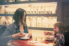 Cute cheerful blond boy with piece of cake and his mom with cup sitting in cafe. Cute cheerful boy with piece of cake and his mom with cup sitting in cafe Royalty Free Stock Photos