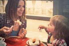 Cute cheerful blond boy with piece of cake and his mom with cup sitting in cafe. Cute cheerful boy with piece of cake and his mom with cup sitting in cafe Royalty Free Stock Image