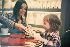 Cute cheerful blond boy with piece of cake and his mom with cup sitting in cafe. Cute cheerful boy with piece of cake and his mom with cup sitting in cafe Stock Images
