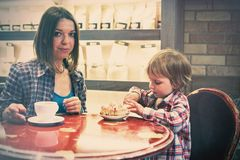 Cute cheerful blond boy with piece of cake and his mom with cup sitting in cafe. Cute cheerful boy with piece of cake and his mom with cup sitting in cafe Stock Photography
