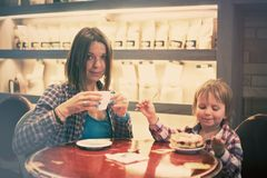Cute cheerful blond boy with piece of cake and his mom with cup sitting in cafe. Cute cheerful boy with piece of cake and his mom with cup sitting in cafe Royalty Free Stock Photo