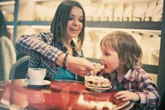 Cute cheerful blond boy with piece of cake and his mom with cup sitting in cafe. Cute cheerful boy with piece of cake and his mom with cup sitting in cafe Stock Image