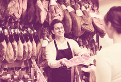 Cute cheerful brunette choosing iberico and serrano jamon. And smiling Royalty Free Stock Photo
