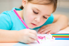 Cute cheerful child drawing using felt-tip pen. While sitting at table stock images