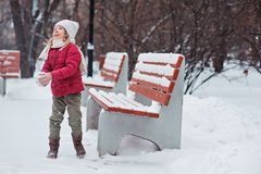 Cute cheerful child girl making snowball in winter snowy park. Cute cheerful child girl in red coat making snowball in winter snowy park near wooden bench Stock Images