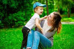Cute cheerful child with mother play outdoors Stock Photos