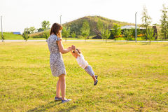 Cute cheerful child with mother play outdoors in park stock photo