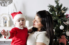 Cute cheerful child in Santa costume with mother Royalty Free Stock Photo