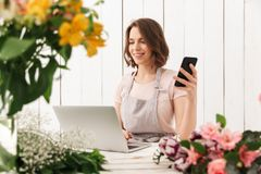 Cute cheerful florist lady using laptop computer chatting by mobile phone. Stock Image