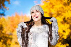 Cute cheerful girl on a background of autumn trees Stock Photos