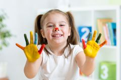 Cute cheerful girl showing her painted hands Royalty Free Stock Images