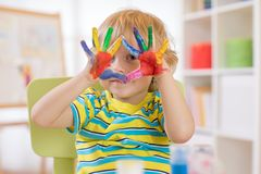 Cute cheerful kid with hands painted in bright colors royalty free stock photography