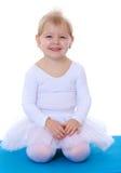 Cute cheerful little ballerina sitting Stock Images