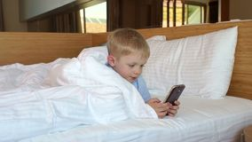 A little boy playing phone at home was lying on the bed under the blanket. Cute cheerful little child playing video games on phone lying on a big white bed stock footage