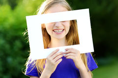 Cute cheerful little girl holding white picture frame in front of her face Stock Image