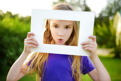 Cute cheerful little girl holding white picture frame in front of her face Royalty Free Stock Photos