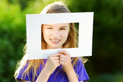 Cute cheerful little girl holding white picture frame in front of her face Stock Images