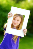 Cute cheerful little girl holding white picture frame in front of her face Royalty Free Stock Photography