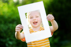 Cute cheerful little girl holding white picture frame in front of her face Stock Photo