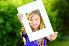 Cute cheerful little girl holding white picture frame in front of her face Royalty Free Stock Images