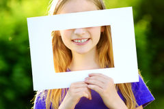 Cute cheerful little girl holding white picture frame in front of her face Stock Photos
