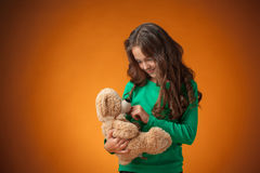 The cute cheerful little girl on orange background Stock Image