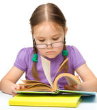 Cute cheerful little girl reading book Royalty Free Stock Images