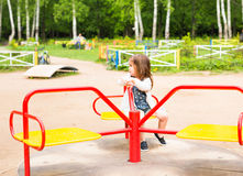 Cute cheerful little girl is riding on merry-go-round stock photography