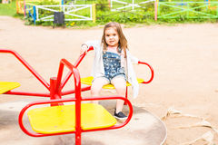 Cute cheerful little girl is riding on merry-go-round royalty free stock image