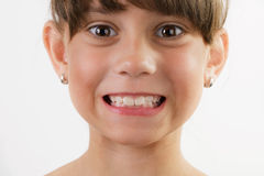Cute cheerful little girl shows teeth royalty free stock images