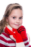Cute cheerful little girl wearing striped knitted sweater, scarf and mittens isolated on white background. Winter clothes. Stock Image