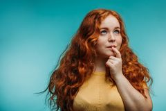 Cute cheerful redhead young girl in yellow t-shirt over blue background with funny face. stock photography