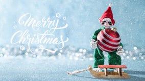 Cute Cheerful Santas Helper Elf Loading Christmas Bauble Onto Santas Sleigh. North Pole Christmas Scene. Santas Workshop. stock image