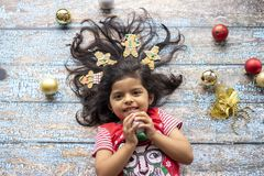 Cute cheerful smiling girl with decorated Christmas hair with gingerbread men royalty free stock image