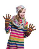 Cute cheerful teenage girl wearing colorful striped sweater, scarf, gloves and hat isolated on white background. Winter clothes. Royalty Free Stock Image