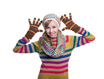 Cute cheerful teenage girl wearing colorful striped sweater, scarf, gloves and hat isolated on white background. Winter clothes. Royalty Free Stock Photo