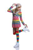 Cute cheerful teenage girl wearing colorful striped sweater, scarf, gloves, hat and white boots isolated. Winter clothes. Stock Photo