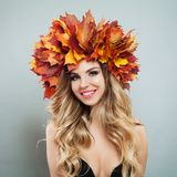 Cute cheerful woman in autumn leaves. Beautiful model face with make up and curly haircut portrait.  royalty free stock image