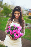 Cute cheerful woman holding flower in pot Stock Photos