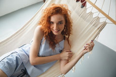 Cute cheerful young redhead lady lies on hammock Stock Images