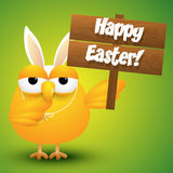 Cute chicken whit a bunny ears costume holding a wooden sign Royalty Free Stock Photography