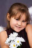 Cute Child. Closeup view of a young girl holding some artificial daisies Stock Photography