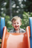 Cute child. Happy,smiling, cute blonde blue eyed caucasian toddler boy wearing plaid shirt climbing up slide Stock Images