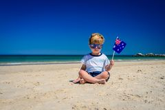 Cute child with Australian flag on Australia day. Cute child with Australian flag  sitting on the sand at the beach on Australia day Royalty Free Stock Photos