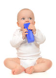 Cute child baby girl toddler sitting and eating blue toy brick Stock Photos